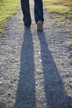 man walking on a gravel road