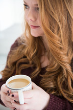 woman in thought holding a cup of coffee
