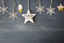 snowflake and star ornament on a wooden background.