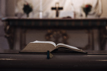 open Bible on a church railing in front of an altar