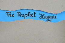 The Prophet Haggai - torn open kraft paper over blue paper with the name of the prophetic book Haggai