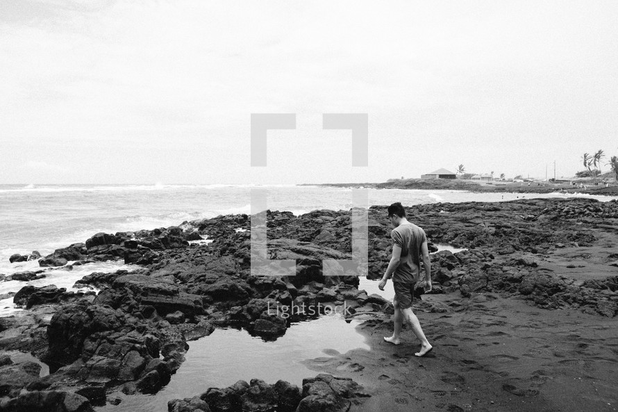 man walking on a rocky beach