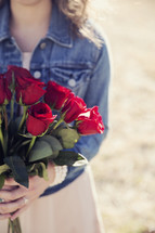 girl holding a bouquet of red roses.