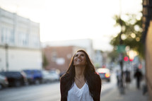 a woman walking down a sidewalk happily looking up.