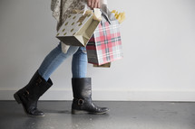 a woman carrying Christmas gift bags