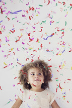 girl child standing under confetti
