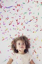 girl child standing under confetti