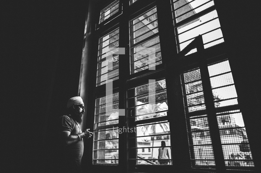 man looking out a window