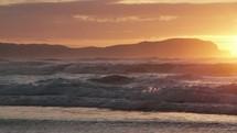 waves washing onto a shore at sunset