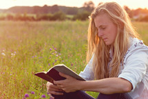 woman reading a Bible in a field of wildflowers