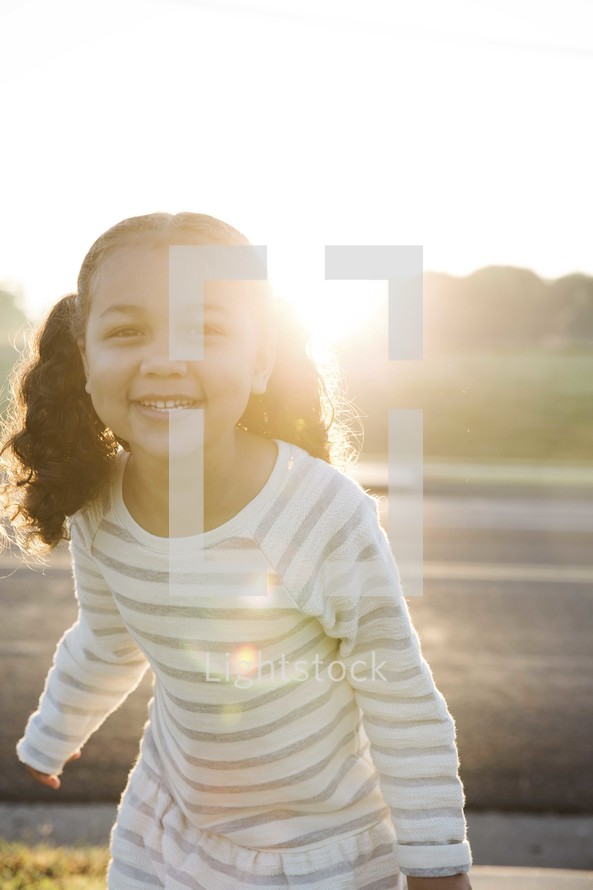 a smiling toddler girl in pigtails laughing in the sun.