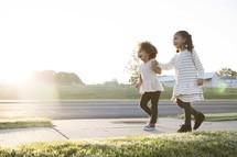 sisters walking holding hands on a sidewalk
