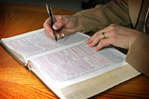 A professional woman studies the Holy Bible during some quiet time set aside in her day - focus point on the woman's hands.