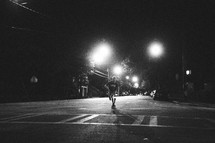 man skateboarding in the middle of the road at night