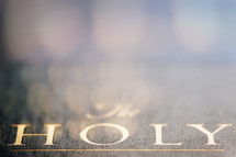 "Gold lettering of the word ""holy"" on a Bible cover."