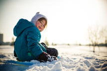 child sitting on a sled in the snow