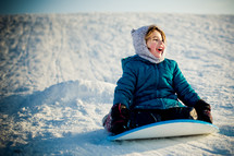 child sledding down a snow covered slope