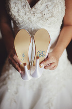 a torso holding her shoes that say I do