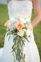 torso of a bride holding a bridal bouquet