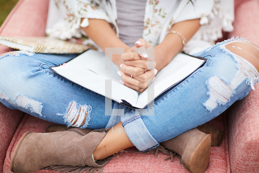 a young woman sitting in a chair with praying hands over the pages of a Bible