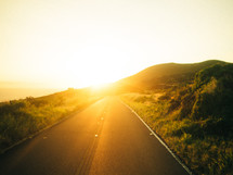 A road leads into the sunset.