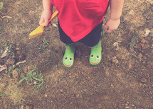 a toddler boy in rain boots playing in dirt