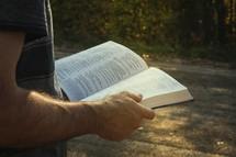 a man reading a Bible outdoors