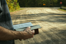 arrow street sign and a man reading a Bible