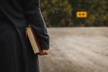 woman holding a Bible and arrow street sign