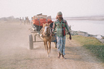 A man leading a horse pulling a wagon