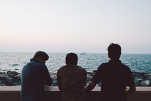three men looking out at the ocean
