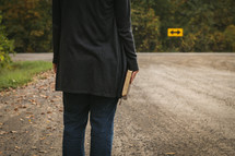 arrow street sign and woman holding a Bible