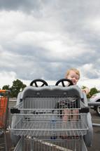 little boy in a shopping cart