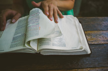 Hands turning the pages of a Bible on a wooden table.