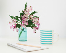 pencil on a spiral notebook, flowers in a vase, and mug