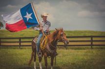 man riding a horse holding a Texas flag