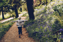 a boy walking on a path in the woods