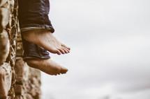 man's dangling bare feet