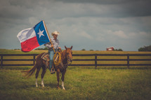 man riding a horse holding a Texas flag