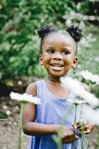 A smiling little girl standing among flowers.