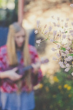 A woman plays a ukulele in a garden.
