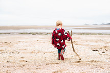 a boy child in rain boots dragging a stick on a beach