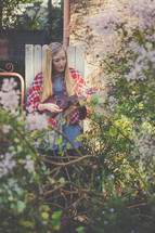 A woman playing a ukulele in a garden.
