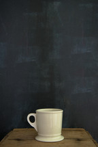 Coffee cup sitting on top of a wooden crate against a chalk wall.