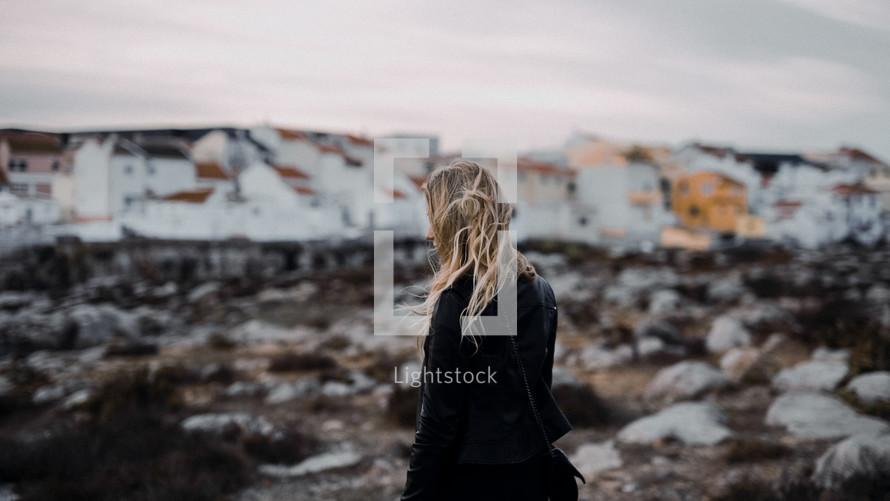 a blonde woman walking on a beach wearing a coat