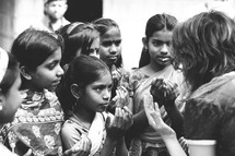 Woman and girl children in prayer on a mission trip