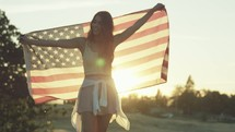 Young Woman Holds Up American Flag As She Walks Toward Camera in Slow Motion