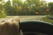 arrow street sign and hand on a steering wheel