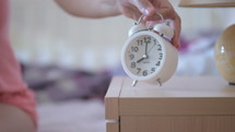 a woman waking up turning off an alarm clock
