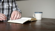 man sitting, open a Bible, and reading